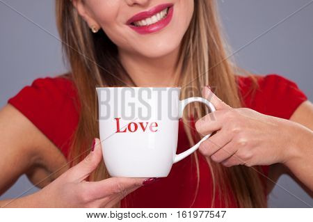 Holiday St.Valentine's Day.Niceattractivebeautiful girlmodel inclined the headholds cup in handswith creative make-upbrightredpink tonescolorsglossy St.Valentine's DaySt.Valentine's Day.