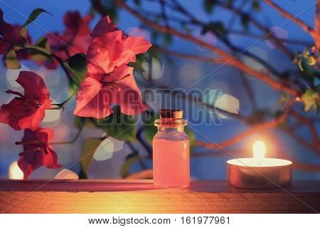 Aroma relaxing low light spa set. Pink tropical flowers, bottle of perfume or massage oil, tea-candle.