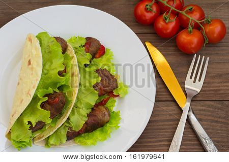 Tortilla with meat wrapped in bacon and herbs. Wooden background. Top view. Close-up