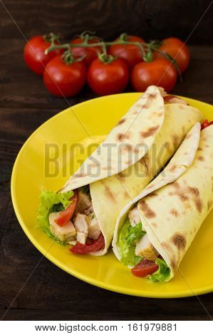 Tortilla with chicken, croutons, mozzarella, tomatoes, bell peppers sauce and greens