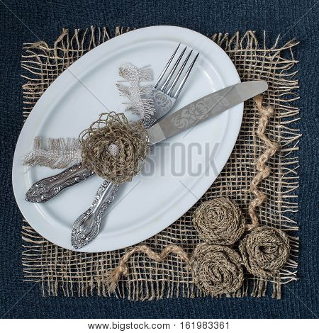Burlap eco-friendly decor. DIY concept. Homemade napkin of burlap with handmade flowers for the table. Plate spoon fork on napkin of burlap. Vintage rustic style. Square image