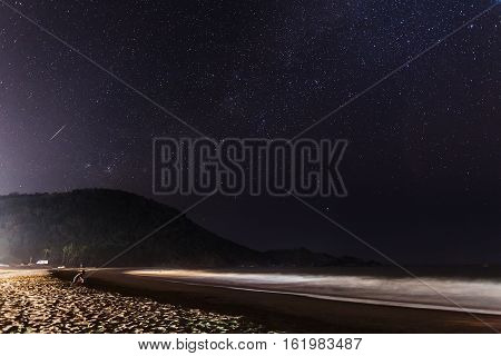 The young man sits at night on the ocean coast under the sky full of stars. Over him in the sky the star (meteor) falls.