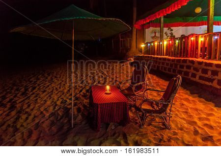 Two armchairs on the beach near restaurant waiting for vacationers. Late evening on a little table before them burning candle.