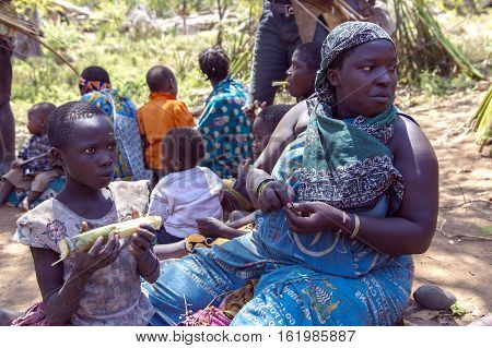 AFRICA, TANZANIA, MAY, 10, 2016 - Portrait woman with a baby who eats sugarcane of the Hadzabe tribe. Hadzabe tribe threatened by extinction in Tanzania, Africa