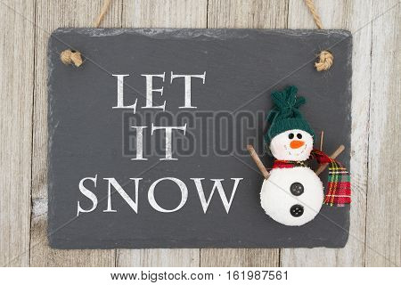 Old fashion Christmas message A retro chalkboard with a snowman hanging on weathered wood background with text Let it Snow