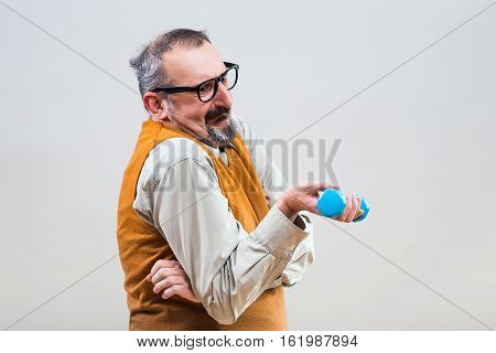 Nerdy businessman is trying to exercise with weights but they are too heavy for him.