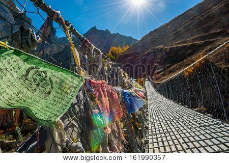 Metal suspension bridge with buddhist praying flags. Annapurna circuit trek.