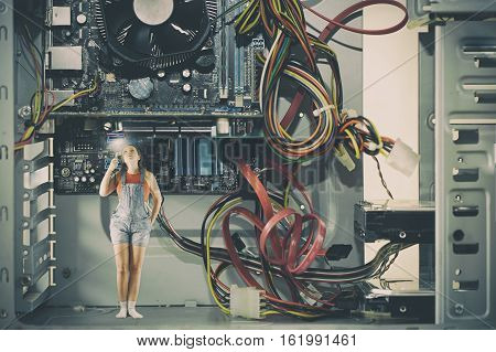 Little female with a flashlight inside a large computer. Computer techologies.