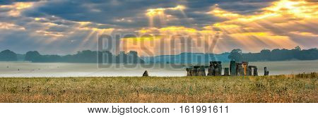 Amesbury Wiltshire United Kingdom - August 14 2016: Cloudy sunrise over Stonehenge - prehistoric megalith monument arranged in circle.