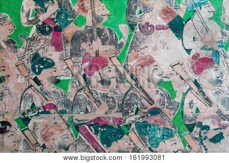 Fresco with many soldiers with guns go in orderly rows walk on a wall of Indian palace in Rajasthan, India. 17th century fresco of Bundi Palace it is situated on hill adjacent to Taragarh Fort