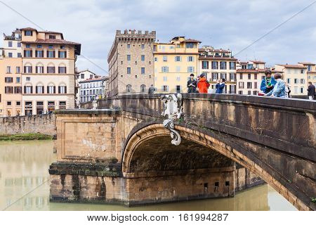 Tourists On Ponte Santa Trinita Over Arno River