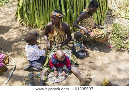 AFRICA, TANZANIA, MAY, 10, 2016 - Woman with small children of the Hadzabe tribe sitting on the ground. Hadzabe tribe threatened by extinction in Tanzania, Africa