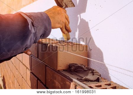 Facing bricklaying construction work manual labor. The construction of the house