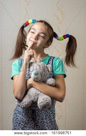 11 Year Old Girl With A Teddy Bear Thoughtfully Looking Up With Her Finger To The Mouth.