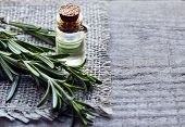 Rosemary essential oil in a glass bottle with fresh green rosemary herb on old wooden table. Rosemary oil for spa,aromatherapy and body care. Extract oil of rosemary. Selective focus. poster