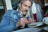 Mature man in coffee shop writing notes on agenda poster