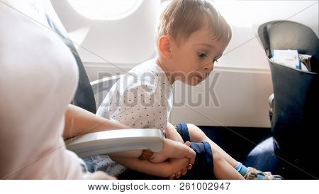 Young Mother Holding By Hand Her Toddler Boy Being Scared Of His First Flight In Airplane