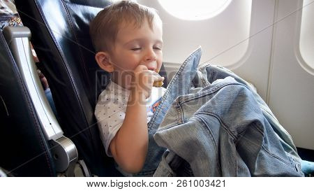 Portrait Of Funny Toddler Boy Eating During Flight In Airplane