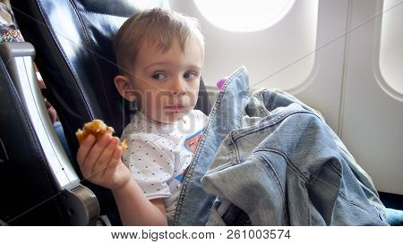 Portrait Of 2 Years Old Toddler Boy Having Snack During Flight In Airplane