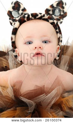 Beautiful four month old baby girl in brown tutu and animal print cat ears with jewels over white background.
