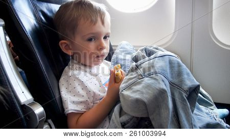 Portrait Of Cute Toddler Boy Having Snack On Long Flight In Airplane
