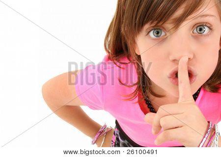 Beautiful 10 year old girl making hush gesture looking up at camera.