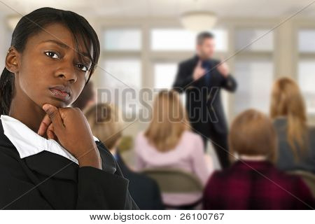 Attractive young business woman at conference meeting.