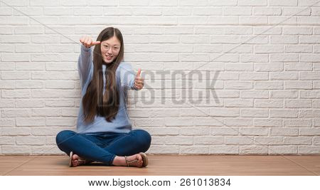 Young Chinese woman sitting on the floor over brick wall approving doing positive gesture with hand, thumbs up smiling and happy for success. Looking at the camera, winner gesture.