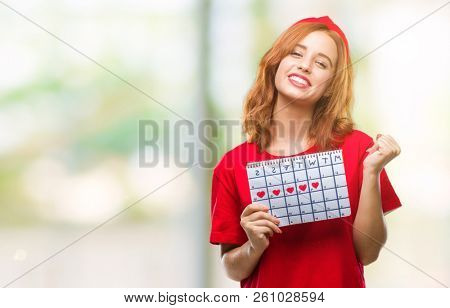 Young beautiful woman over isolated background holding menstruation calendar screaming proud and celebrating victory and success very excited, cheering emotion