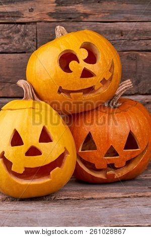 Three Funny Halloween Pumpkins. Funny Jack O Lntern Halloween Pumpkins On Wooden Background. Hallowe