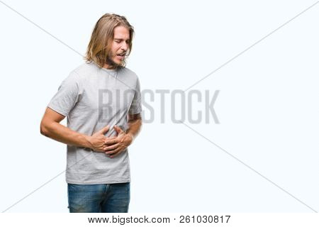Young handsome man with long hair over isolated background with hand on stomach because indigestion, painful illness feeling unwell. Ache concept.