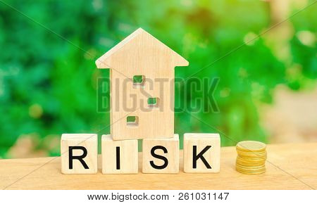 Wooden House And Cubes With The Word Risk. The Concept Of Risk, Loss Of Real Estate. Property Insura