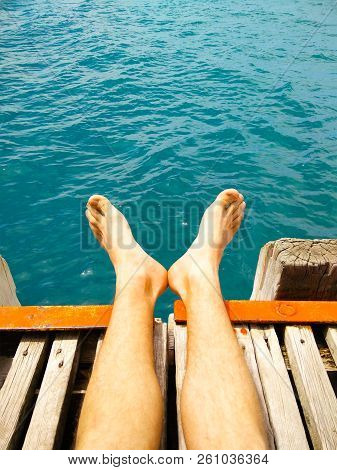 Guy Is Sitting On The Pier. Blue Ocean. Young Man Relax Siting On Pier.