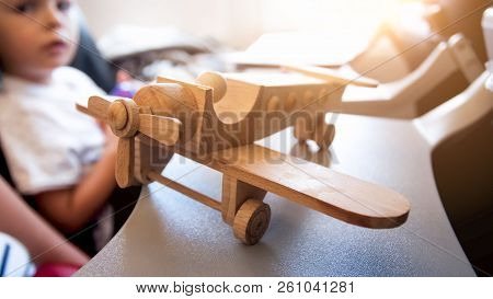 Closeup Image Of Wooden Airplane Miniature Against Little Boy Sitting In Passenger Seat During Fligh