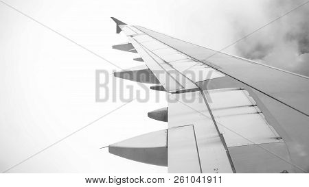 Black And White Image Of Airplane Flying Through Clods