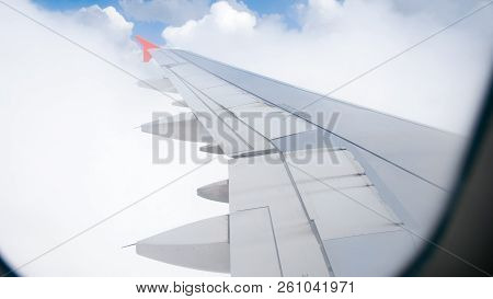 View From Passenger Seat Of Airplane Flying Through Clouds