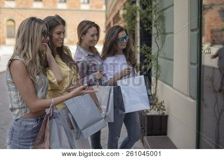 Happy Woman With Shopping Bags Pointing Finger At The Shop Window. Shopping With A Smile. Shopping F