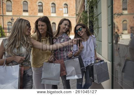 Happy Woman With Shopping Bags Pointing Finger At The Shop Window.shopping With A Smile. Shopping Fu