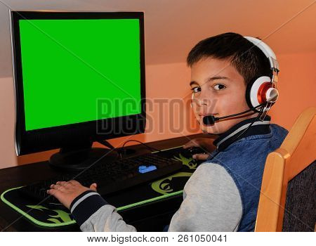 A Young Gamer Boy Playing Video Games On Computer Wearing Headphones And Colorful Keyboard