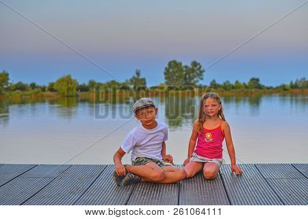 Children Sitting On Pier. Siblings. Two Children Of Different Age - Elementary Age Boy And Preschool