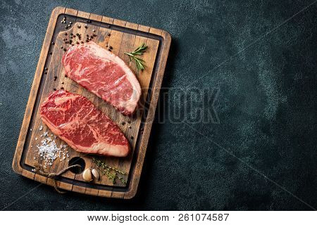 Fresh Raw Prime Black Angus Beef Steaks With Spices On Wooden Board: Striploin, Rib Eye. Top View Wi