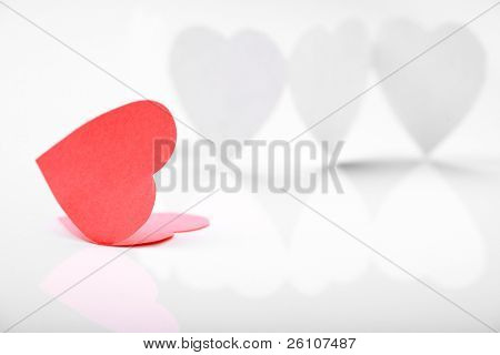Photo of white paper hearts in chain with one of them red being on a foreground.