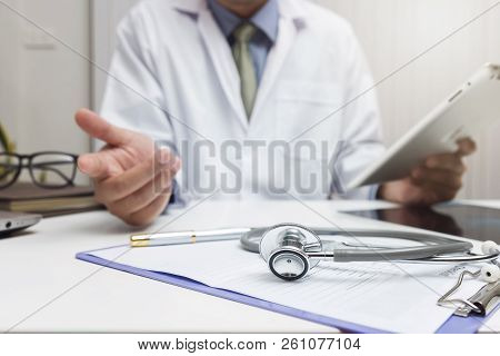 Doctor Using Laptop And Smartphone In Office.