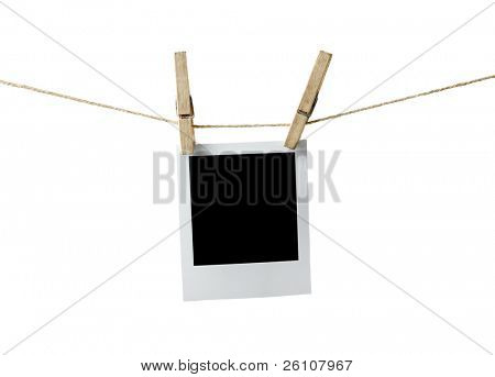 Blank instant photo hanging on the clothesline. Isolated on white background.