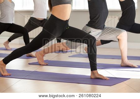 Group Of Sporty People Practicing Yoga, Doing Warrior One Exerci