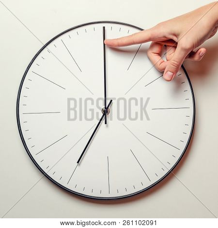 Woman Hand Stop Time On Round Clock, Female Finger Takes The Minute Arrow Of The Clock Back, Time Ma