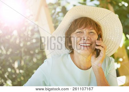 Aged Woman Talking On The Phone. Old Lady In The Park. Sunny Day, Happy Mood. Upset Senior Woman Wit