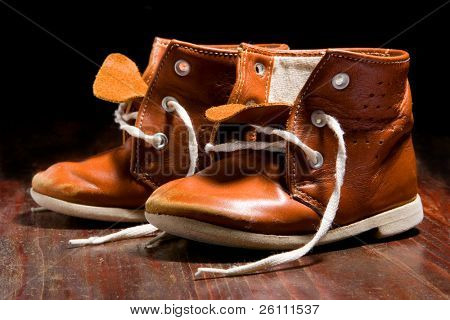 old child's boot on wooden background