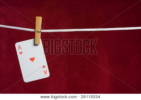 heart ace with clothes peg  rope on red background