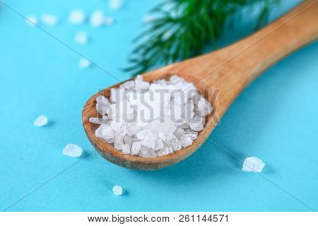 Crystals Of Large Sea Salt In A Wooden Spoon And Dill On A Blue Table.